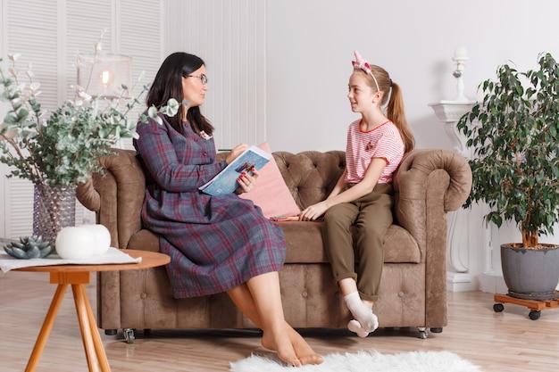 Tienermeisje bij ontvangst bij de psychotherapeut. psychotherapie sessie voor kinderen. de psycholoog werkt met de patiënt. meisje lachend zittend op een bank naast een zittende vrouwelijke arts therapeut