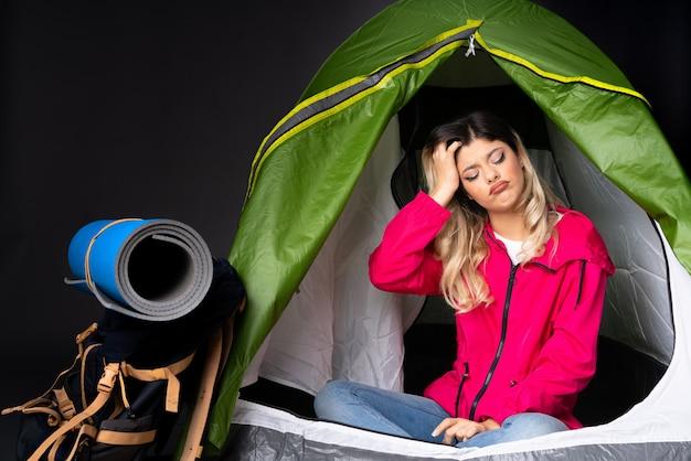 Tienermeisje binnen een het kamperen groene tent op zwarte muur met een uitdrukking van frustratie en niet begrijpend