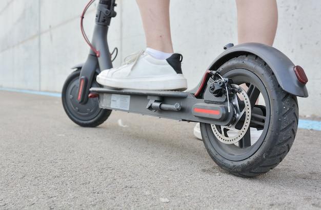 Tienermeisje circuleert met een elektrische scooter