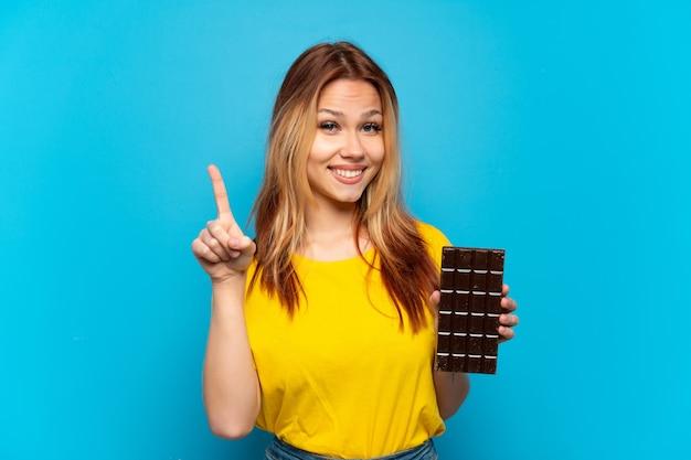 Tienermeisje dat chocolade vasthoudt over een geïsoleerde blauwe achtergrond die een vinger laat zien en optilt in teken van het beste