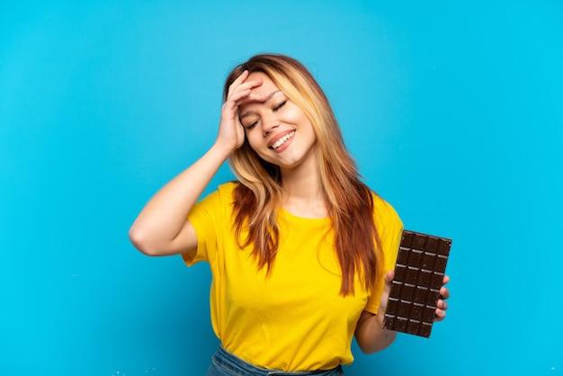 Tienermeisje dat chocolade vasthoudt over geïsoleerde blauwe achtergrond die veel lacht