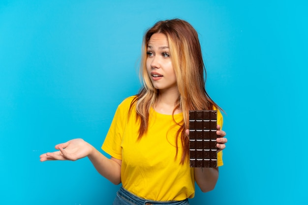 Tienermeisje dat chocolade vasthoudt over geïsoleerde blauwe achtergrond met verrassingsuitdrukking terwijl ze opzij kijkt