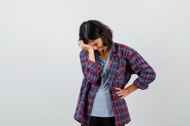 Tienermeisje dat de ogen bedekt met de hand, de hand op de taille houdt in een geruit overhemd en er boos uitziet, vooraanzicht.