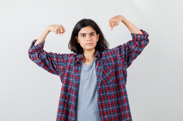 Tienermeisje dat de spieren van de armen in vrijetijdskleding toont en er sterk uitziet, vooraanzicht.