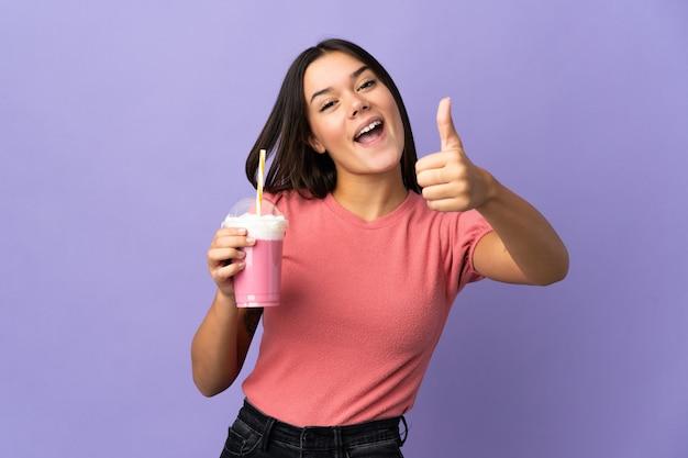 Tienermeisje dat een aardbeimilkshake met omhoog duimen houdt omdat er iets goeds is gebeurd