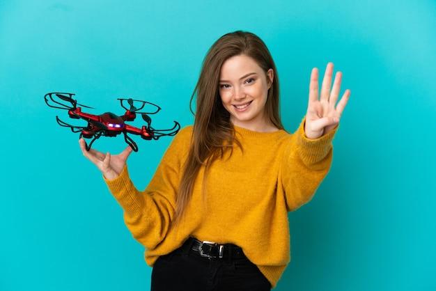Tienermeisje dat een drone over geïsoleerde blauwe achtergrond gelukkig houdt en vier met vingers telt count