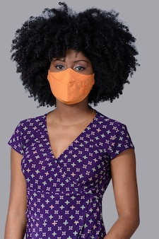 Tienermeisje dat gezichtsbeschermingsmasker draagt tegen covid-19 geïsoleerd op een grijze achtergrond