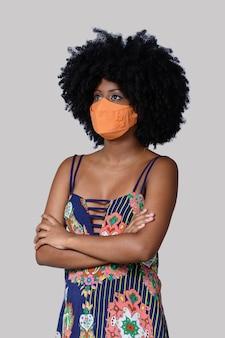 Tienermeisje dat gezichtsbeschermingsmasker draagt tegen covid19 geïsoleerd op een grijze achtergrond