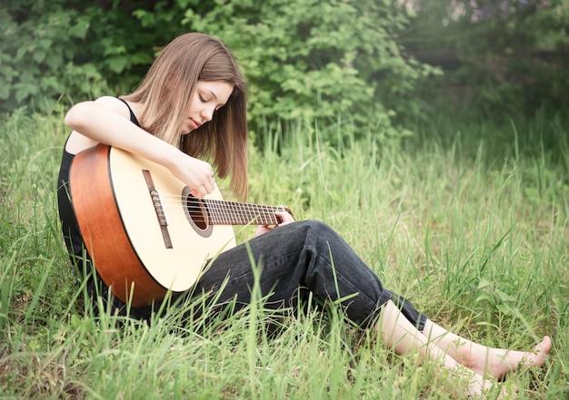 Tienermeisje dat gitaar speelt in het park
