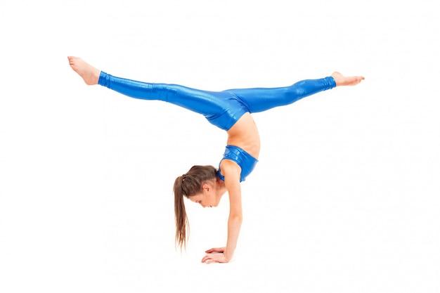 Tienermeisje dat gymnastiekoefeningen doet die op wit worden geïsoleerd
