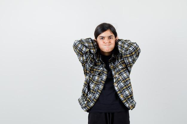 Tienermeisje dat haar haar in een casual shirt schikt en er geïrriteerd uitziet, vooraanzicht.