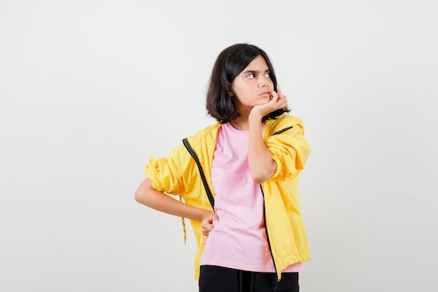 Tienermeisje dat haar tanden controleert, wegkijkt in t-shirt, jas en verveeld kijkt. vooraanzicht.