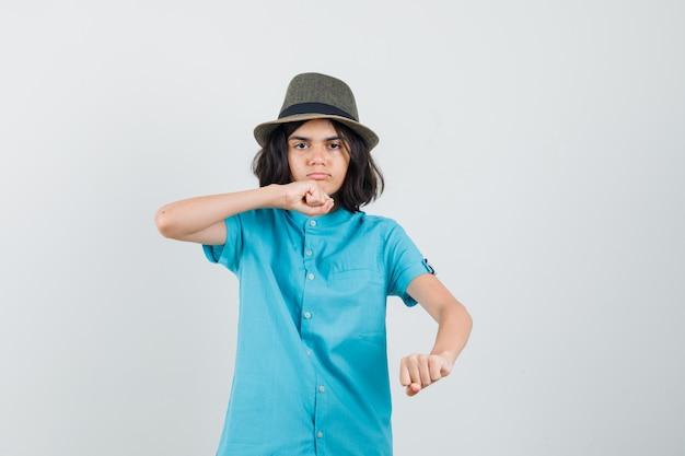 Tienermeisje dat haar vuisten opheft om in blauw overhemd te vechten en ernstig te kijken