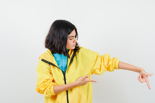 Tienermeisje dat in gele jas naar beneden wijst en resoluut kijkt. vooraanzicht.