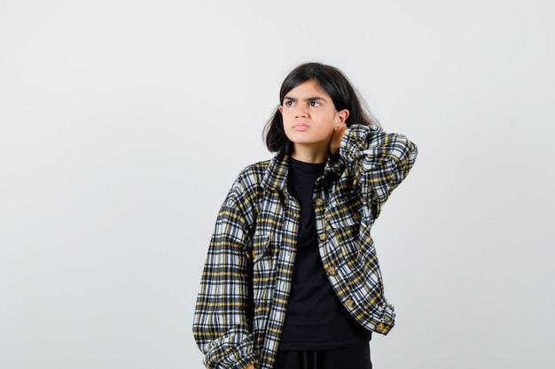 Tienermeisje dat lijdt aan nekpijn, wegkijkt in een casual shirt en er onwel uitziet. vooraanzicht.