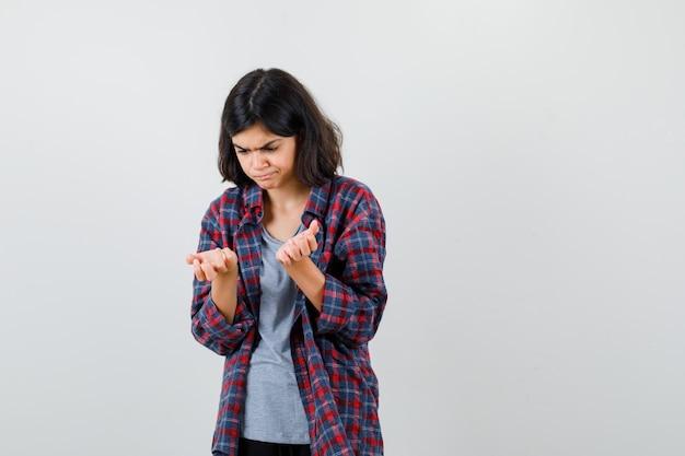 Tienermeisje dat naar haar handen kijkt, zijwaarts in een geruit overhemd staat en er somber uitziet.