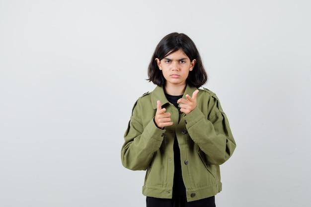 Tienermeisje dat naar voren wijst in een legergroen jasje en er ongezellig uitziet. vooraanzicht.