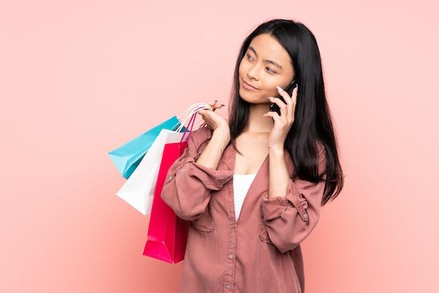 Tienermeisje dat op roze holdings het winkelen zakken wordt geïsoleerd en een vriend met haar celtelefoon roept
