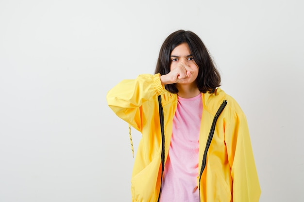 Tienermeisje dat over haar vuist in t-shirt, jasje kijkt en woedend, vooraanzicht kijkt.