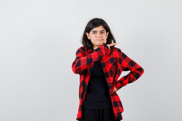 Tienermeisje dat pistoolgebaar in casual shirt toont en verbaasd kijkt, vooraanzicht.