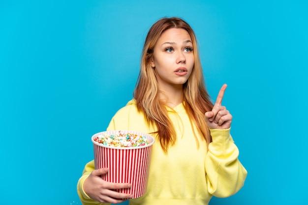Tienermeisje dat popcorns vasthoudt over geïsoleerde blauwe achtergrond en denkt aan een idee dat de vinger omhoog wijst