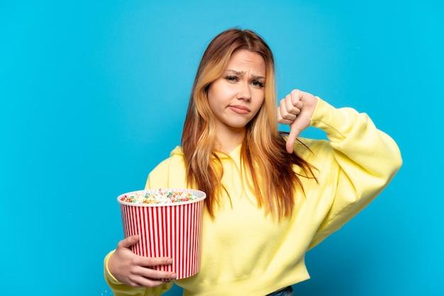 Tienermeisje dat popcorns vasthoudt over geïsoleerde blauwe achtergrond met duim omlaag met negatieve uitdrukking