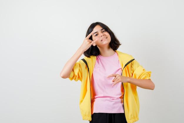 Tienermeisje dat rock n roll-gebaar in t-shirt, jas toont en er vrolijk uitziet, vooraanzicht.