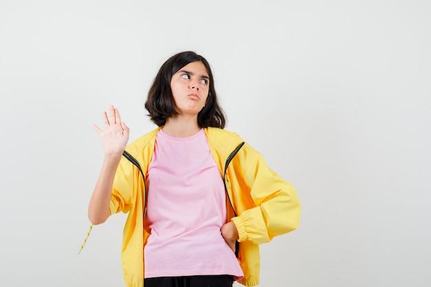 Tienermeisje dat stopgebaar toont, hand op taille houdt in geel trainingspak, t-shirt en verbaasd kijkt, vooraanzicht.