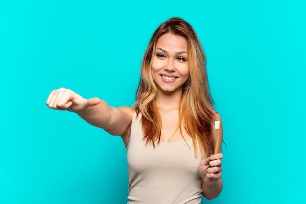 Tienermeisje dat tanden poetst over geïsoleerde blauwe achtergrond die een duim omhoog gebaar geeft