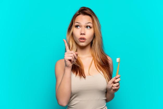 Tienermeisje dat tanden poetst over geïsoleerde blauwe achtergrond die een idee denkt dat de vinger omhoog richt