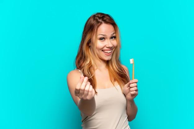 Tienermeisje dat tanden poetst over geïsoleerde blauwe achtergrond die geldgebaar maakt
