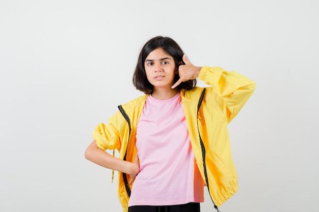 Tienermeisje dat telefoongebaar in geel trainingspak, t-shirt toont en er vredig uitziet, vooraanzicht.