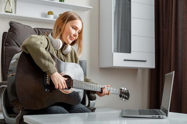 Tienermeisje dat thuis gitaar leert spelen met behulp van online lessen. hobby afstandsbediening muzikaal onderwijs akoestische gitaar. jonge vrouw speelt akoestische gitaar thuis voor online publiek op laptop.
