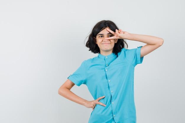 Tienermeisje dat v-teken op haar oog in blauw overhemd toont en vrolijk kijkt.