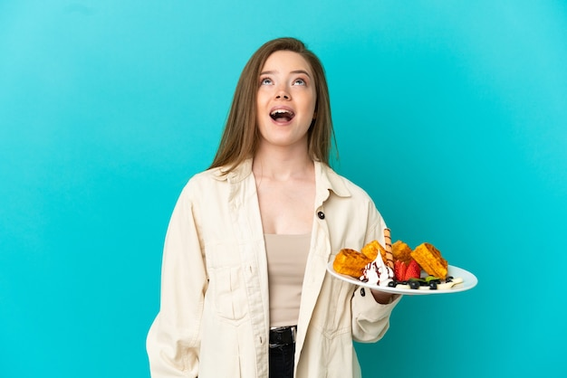Tienermeisje dat wafels vasthoudt over geïsoleerde blauwe achtergrond en omhoog kijkt en met een verbaasde uitdrukking