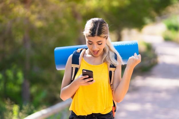 Tienermeisje die bij in openlucht wandelen verrast en een bericht verzenden