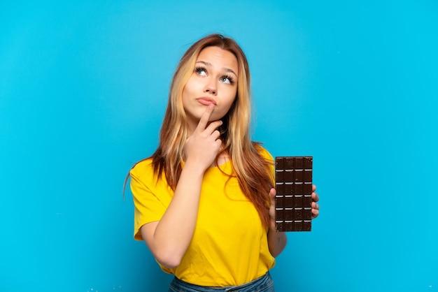 Tienermeisje die chocolade geïsoleerd houden