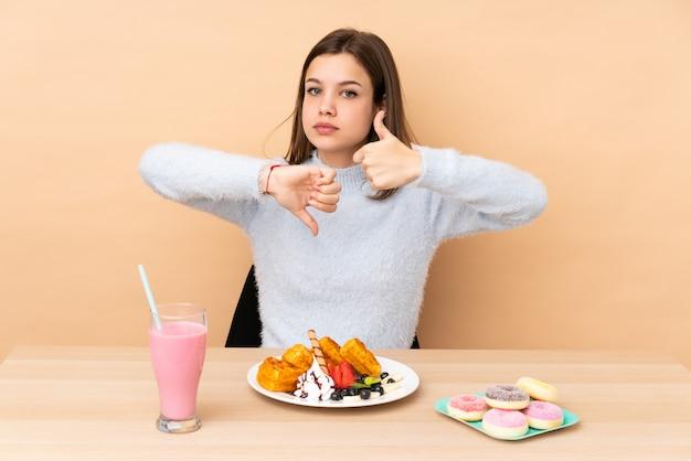 Tienermeisje die die wafels eten op beige muur worden geïsoleerd die goed-slecht teken maken. onbeslist tussen ja of niet