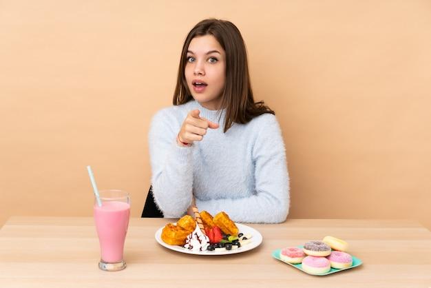 Tienermeisje die die wafels eten op beige muur worden verrast en voorzijde worden verrast