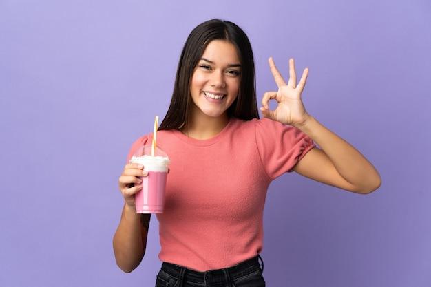 Tienermeisje die een aardbeimilkshake houden die ok teken met vingers tonen
