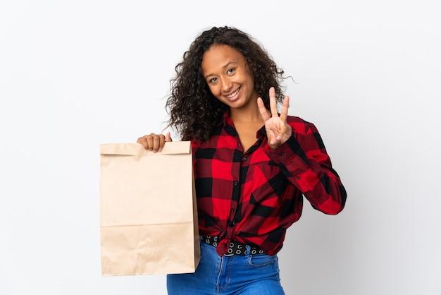 Tienermeisje die een boodschappentas houden aan afhaalmaaltijden geïsoleerd op een witte muur gelukkig en drie met vingers tellen