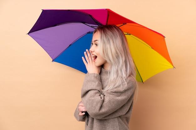 Tienermeisje die een paraplu over muur houden die met wijd open mond schreeuwen