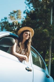 Tienermeisje die gelukkig door de auto golven.