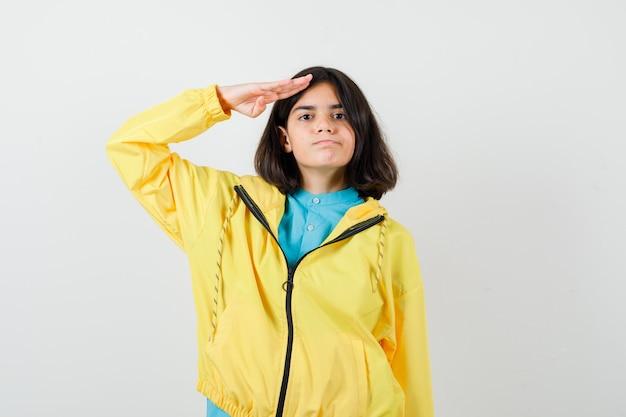 Tienermeisje die groetgebaar in geel jasje tonen en zelfverzekerd, vooraanzicht.