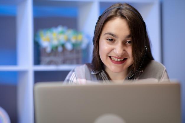 Tienermeisje die haar huiswerk online doen en aan hoofdtelefoons luisteren. jonge studente gebruikt haar laptop.