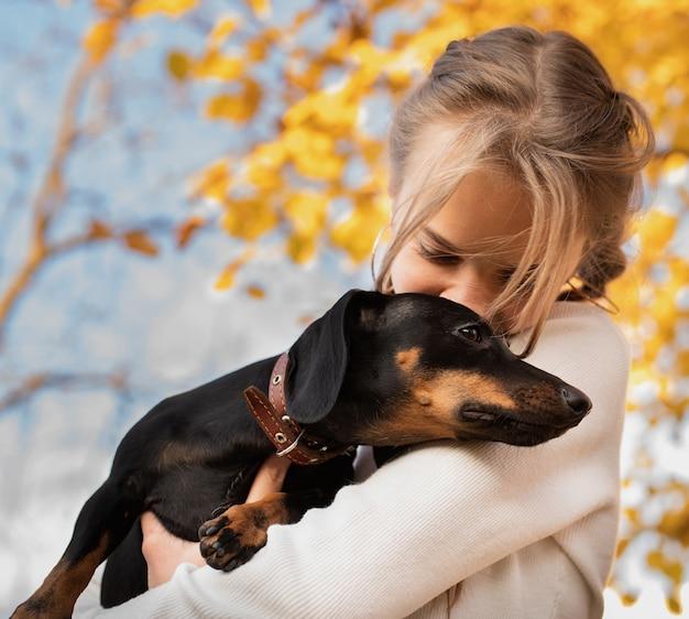 Tienermeisje die haar tekkelhond in openlucht koesteren