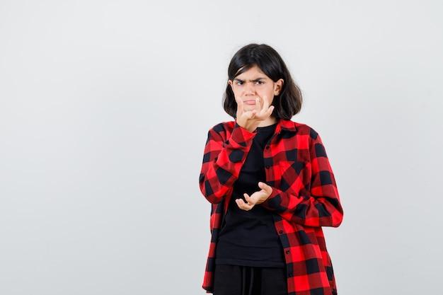 Tienermeisje die handen op een onwetende manier in een casual shirt uitrekt en er verbaasd uitziet, vooraanzicht.