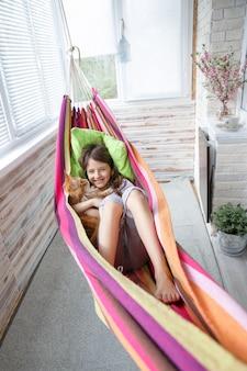Tienermeisje die in een hangmat samen in uw favoriete kat maine wasbeer liggen
