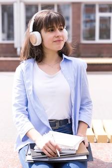 Tienermeisje die in hoofdtelefoons met boeken zitten