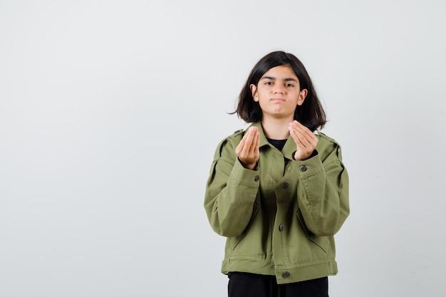 Tienermeisje die italiaans gebaar in legergroen jasje doen en ontevreden kijken. vooraanzicht.